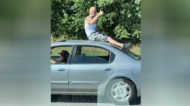 Driver charged after man seen riding atop vehicle on